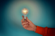 Man Holds A Lightbulb In Hand. Concept Of Creativity And Solution. Cyan Background