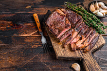 Roasted And Sliced Rib Eye Beef Meat Steak On A Wooden Cutting Board With Thyme. Dark Wooden Background. Top View. Copy Space