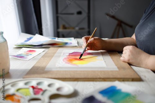 Fototapeta Hands of artist holding brush with watercolor painting obraz