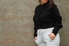 Fashion Image Of Plus Size Woman Wearing Black Wool Top And Light Trainer Pants Leaning Against Concrete Wall With Copy Space