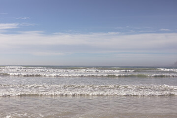 View of beautiful waves of the sea and the beach against blue sky