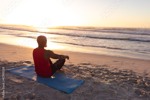 Senior african american man meditating and practicing yoga while sitting on yoga mat at the beach