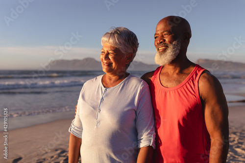 Senior african american couple smiling while standing on the beach