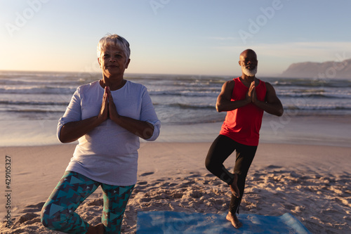 Senior african american couple with folded hands meditating and practicing yoga together at the beac