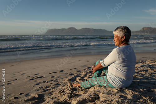 Senior african american woman smiling while sitting on the beach
