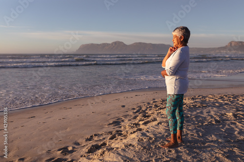 Thoughtful senior african american woman with hand on her chin standing on the beach