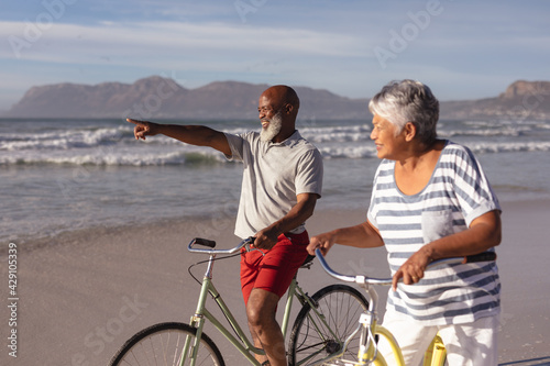 Senior african american couple with bicycles pointing towards a direction at the beach