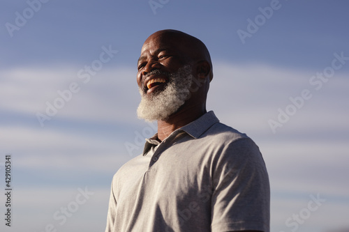Senior african american man smiling while standing on the beach