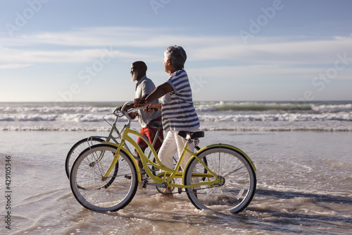 Happy senior african american couple with bicycles walking together on the beach