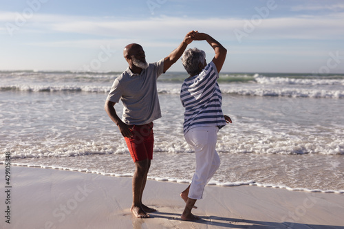 Happy senior african american couple dancing together on the beach