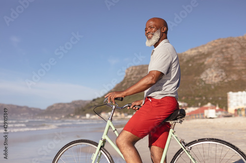 Senior african american man sitting on bicycle smiling on the beach