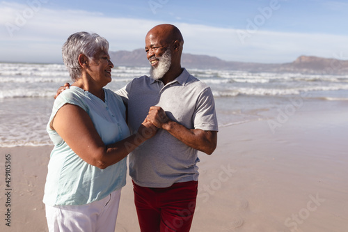 Happy senior african american couple embracing each other on the beach