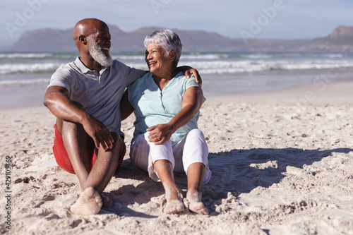 Senior african american couple smiling while looking at each other sitting on the beach