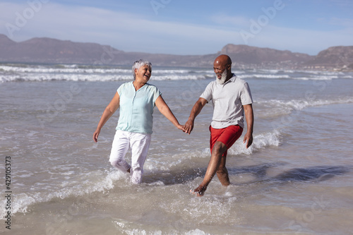 Happy senior african american couple holding hands and having fun on the beach