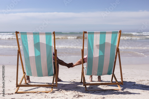 Rear view of senior african american couple holding hands while sitting on deck chairs at the beach