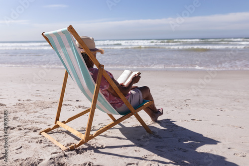 Senior african american woman reading a book while sitting on deck chair at the beach