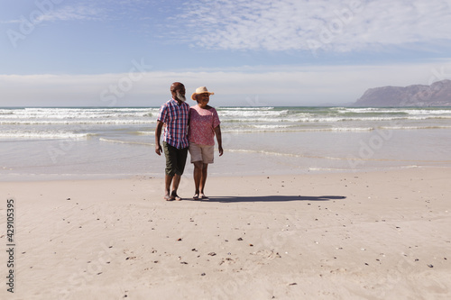 Happy senior african american couple walking together on the beach