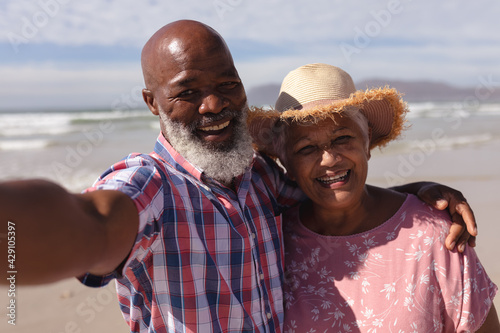 Portrait of happy senior african american couple taking a selfie at the beach