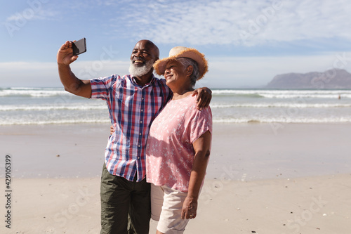 Happy senior african american couple taking a selfie from smartphone on the beach