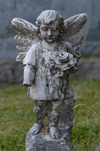 Stone Angel Watching Over A Quiet Cemetery In Quebec, Canada. Years Of Being Out In The Elements Are Shown In The Wear On The Statute And The Missing Forearm.