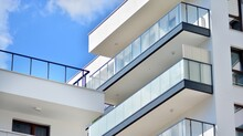 A Fragment Of Modern Architecture, Walls And Glass. Windows And Balconies Of A Residential Building Against A Blue Sky. Detail Of New Luxury House And Home Complex. Part Of City Real Estate Property A