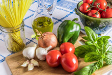 Fresh Italian Ingredients On A Wooden Cutting Board:vine Ripe Tomatoes, Green Bell Pepper, Fresh Basil, Onion And Garlic Along With Dried Angel Hair Pasta And Olive Oil On A Blue And White Tablecloth.