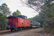 Old Fashioned Red Caboose On The End Of A Train Going Around The Bend