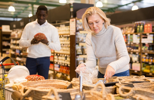 Smiling middle aged woman making purchases in grocery store, filling polybag with groats