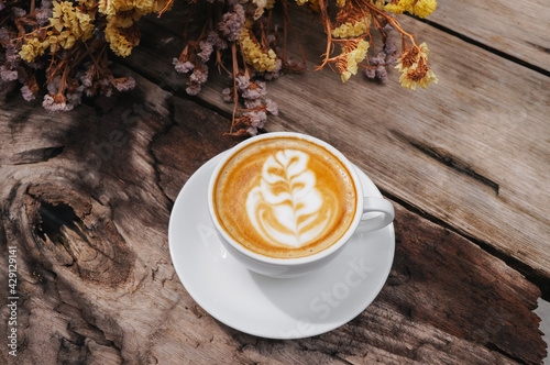 Fotografia Cappuccino coffee latte art, Warm coffee in mug on white plate with Dried flowers background