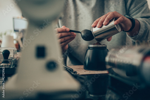 Fotomural Barista measure coffee powder and brewing black moka coffee using moka coffee maker