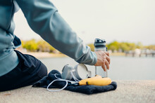 Sport Man Sitting After Running And Holding Water Bottle Drink. Sport Thirsty And Resting After Exercise.