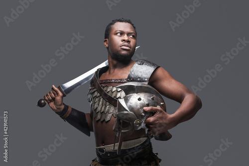 Combative black gladiator holding sword on his shoulder Fototapeta