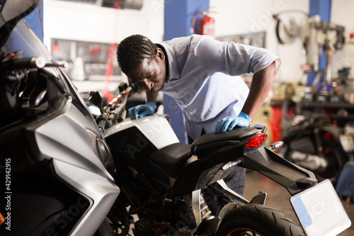 Fotografia Afro american man working at restoring motorbike in motorcycle workshop