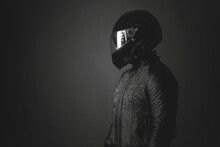 Motorbiker Is Looking Aside On A Dark Background With A Copy Space. Side View.