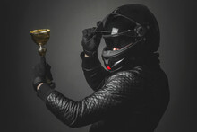 Motorbiker With A Golden Cup Award Trophy In Hand Is Turning Around And Open A Helmet Visor. Race Winner Concept.