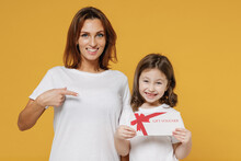 Happy Woman In Basic White T-shirt Child Baby Girl 5-6 Years Old Hold Gift Certificate Coupon Voucher Card. Mom Little Kid Daughter Isolated On Yellow Color Background Studio Mother's Day Love Family