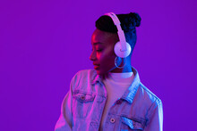 Young African American Woman Wearing Headphones Listening To Music In Futuristic Purple Cyberpunk Neon Light Background
