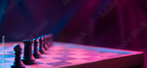 Fotografia Chess pieces on a chessboard on a dark background shot in neon pink-blue colors