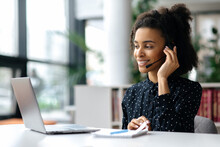 African American Friendly Young Woman With Headset, Call Center Worker, Consultant, Business Person, Looks At The Laptop Screen, Talking With Colleagues Or Clients By Video Call, Conducts Consultation