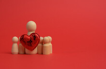 Wooden Small Figurines Of A Family And A Red Heart On A Red Background