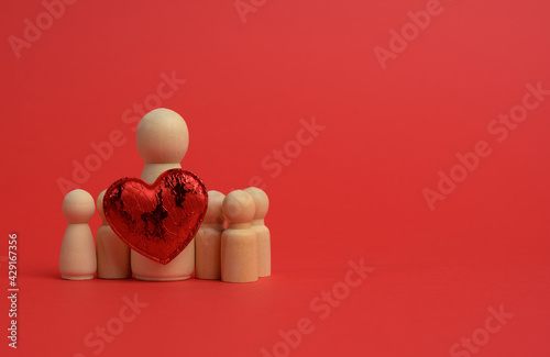 Fototapeta wooden small figurines of a family and a red heart on a red background