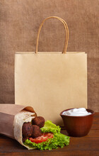 Fastfood Delivery Of Falafel Pita Rollin Craft Paper Bag. Yogurt Sauce In Clay Bowl On Brown Board With Burlap Background. Falafel Sandwich With Tomato And Green Salad. Jewish Cuisine. Place For Logo