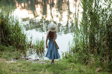 A Cute Girl In A Long Blue Dress And Straw Hat Stands On The Shore Of The Lake. Back Of A Child In The Public Park With Water, Bushes, Green And Dried Grass In Summer. Young Beautiful Lady On Walking.