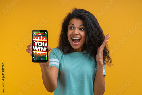 Fotografering Girl being happy winning bet in online sport gambling application on her mobile