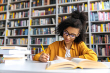 Teenage African American Female Student Studying While Sits At The Table In The College Library, Reads Books To Searching Information For A Lesson Or Exam, Doing Homework And Notes, Gaining Knowledge