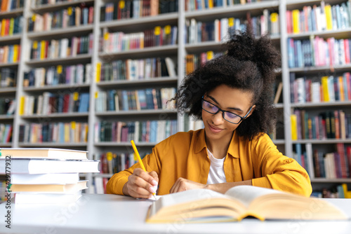 Obraz na płótnie Teenage african american female student studying while sits at the table in the