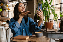 Black Young Woman Blowing Air Kiss While Making Video Call In Cafe