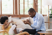Cheerful African American Father Playing Airplane Toys With His Little Son On Sofa At Home.