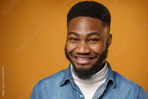 Portrait of young handsome african american guy against yellow background - fototapety na wymiar