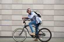 Joyful Black Guy With Backpack And Headphones Riding Bicycle Near Brick Wall On City Street